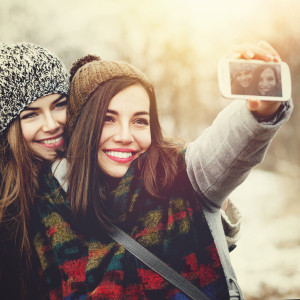 Two teenage girls taking a selfie outdoors in winter
